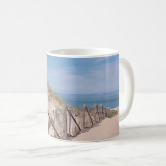 Strandstaket och sandig strand på uddtorsk kaffemugg