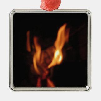 Suddigt flammar i en brinna spis på svart silverfärgad fyrkantigt julgransprydnad