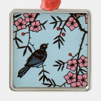 Svart fågel i rosa körsbärsrött blommarträd på julgransprydnad metall