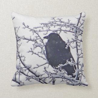 Svart fågel mellan snöig grenar kudde