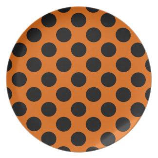 Svart polka dots på orangen tallrik