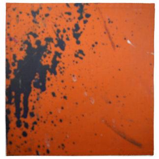 Svarten målar splatteren på orangen tygservett