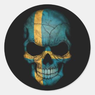 Svenskflaggaskalle på svart runt klistermärke