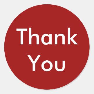 Tackklistermärkear på röd bakgrund runt klistermärke