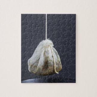 Tea hänger lös hängs i en kopp pussel med foto