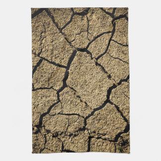 Torrt land med knäckt jord i torka kökshandduk