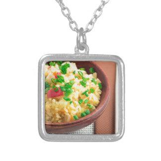 Träbunke av lagade mat ris och grönsaker silverpläterat halsband