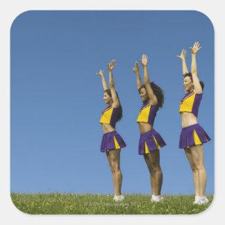 Tre kvinnliga hejaklacksledarear som in står, ror fyrkantigt klistermärke