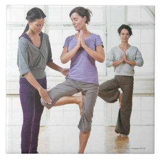 Tre kvinnor som övar yoga kakelplatta