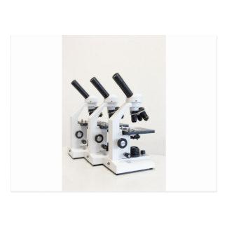 Tre mikroskop i en ro som isoleras på bakgrund vykort