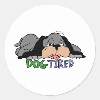 Tröttad hund runt klistermärke
