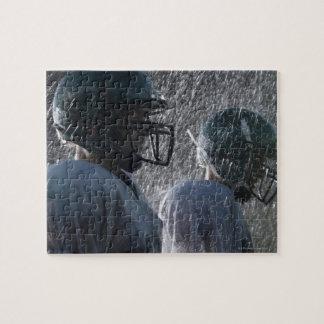 Två amerikanfotbollsspelare regnar in, sidan pussel
