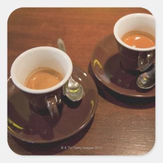 två koppar av nytt bryggat espressokaffe på a fyrkantigt klistermärke