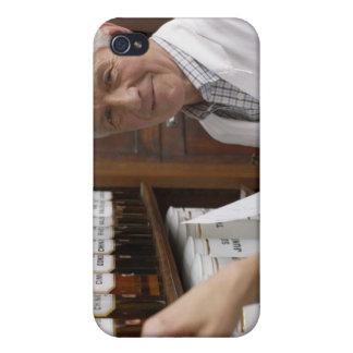 Två pharmacists framme av en hylla med tins iPhone 4 cover