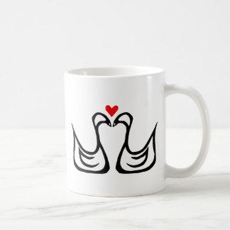 Två svanar och en hjärtamugg kaffemugg