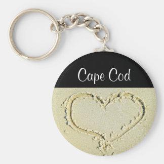 Uddtorskhjärta på en sandig strandnyckelring rund nyckelring