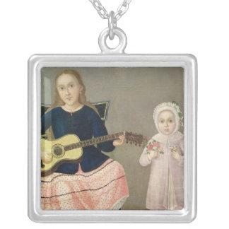 Ung flicka med en gitarr och ett barn med a silverpläterat halsband