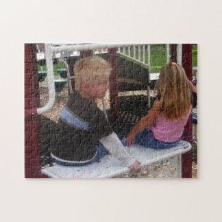 Ungar som sitter på lekplatsskyltfönsterpussel pussel