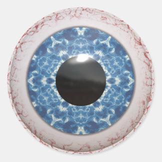 Utåtbuktat blodsprängt blåttöga runt klistermärke