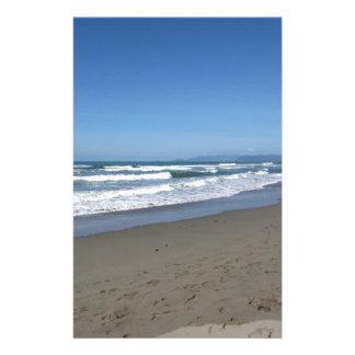 Vågar av havet på sanden sätter på land brevpapper