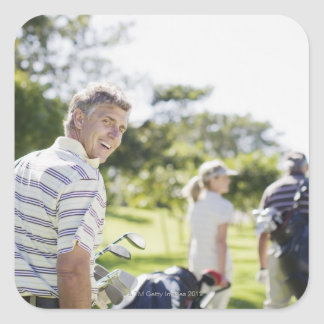 Vänner som bär golf, hänger lös fyrkantigt klistermärke