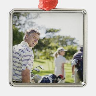 Vänner som bär golf, hänger lös julgransprydnad metall