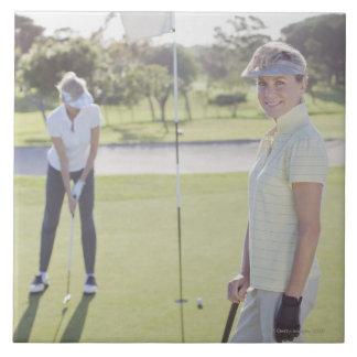 Vänner som leker golf kakelplatta