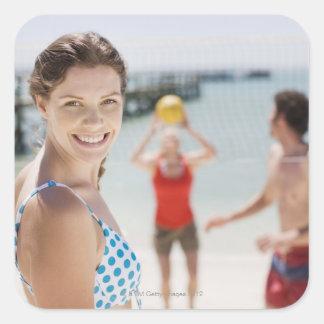 Vänner som leker volleyboll på stranden fyrkantigt klistermärke