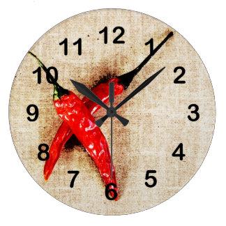 varma röda chilipeppar tar tid på stor klocka