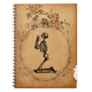 Vintage som knäfaller den skelett- anteckningsbok med spiral