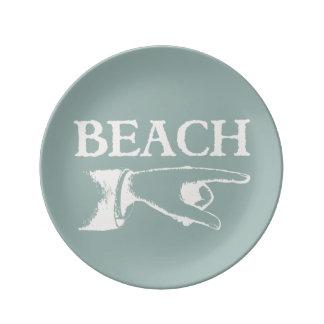 Vintage som pekar stranden, undertecknar porslinstallrik