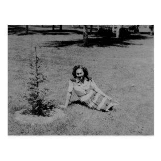Vintagefoto av en kvinnasitta vid lite ett träd vykort