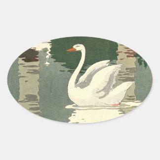 Vitsvan reflekterad på sjön ovalt klistermärke